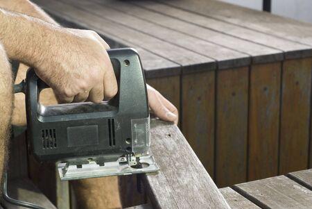 resale: Hand holding jigsaw sawing board. Horizontally framed shot.