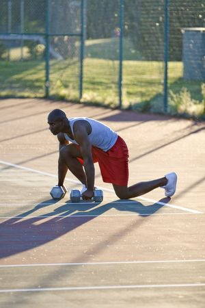vertically: A fit man is crouching down on a tennis court.  He is holding weights in his hands.  He is looking intensly away from the camera.  Vertically framed shot.