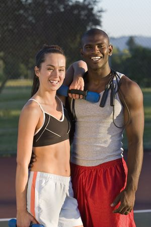 An attractive, fit couple is standing together on a tennis court.  They are holding their workout gear and smiling at the camera.  Vertically framed shot. Stock Photo