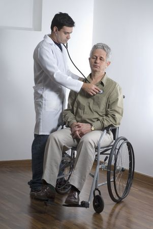 vertically: A patient is sitting in a wheelchair at a doctors office.  The doctor is listening to his heart.  The doctor is looking at the patient and the patient is looking away from the camera.  Vertically framed shot. Stock Photo