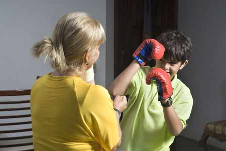 boxing boy: A woman and her son are playing and pretending to box each other.  He is wearing boxing gs.  They are smiling and looking at the camera.  Horizontally framed shot. Stock Photo