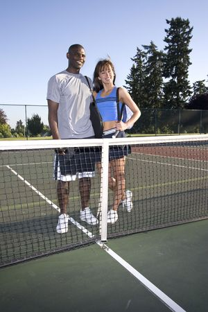 A young, active couple is standing on a tennis court.  They are wearing tennis clothes and smiling at  the camera.    Vertically framed photo.