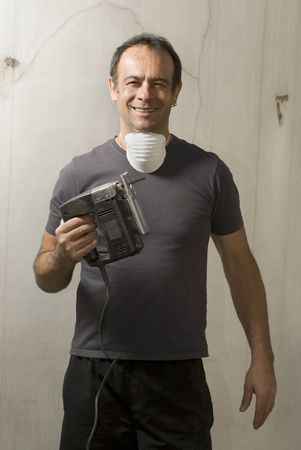 jig saw happiness: Man standing holding jigsaw with mask around neck. He is looking at camera and smiling. Vertically framed shot.