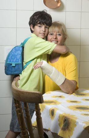 台所のテーブルでは、少年と彼の母親をハグします。 彼らは彼の母を見ています。 垂直方向にフレーム ショット。