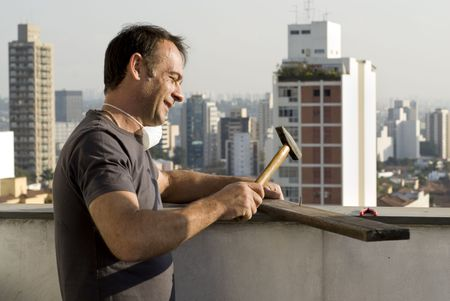 resale: Man wearing paint mask around his neck is hammering a nail into a board with a hammer.  He is smiling. Buildings in the background. Horizontally framed shot.