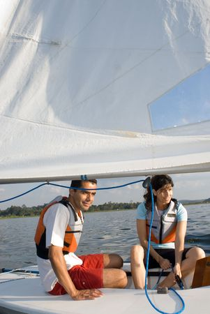 vertically: A woman and man are sitting inside a sailboat.  They are smiling and looking away from the camera.  Vertically framed shot.