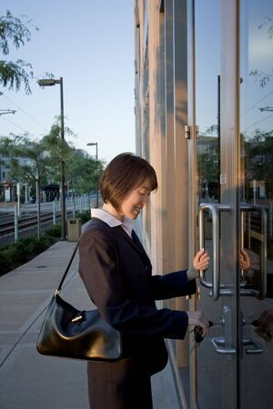 large doors: A woman, standing in front of two large glass doors, unlocking them. away from the camera. Vertically framed shot. Stock Photo