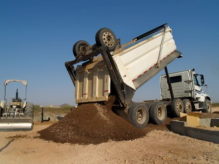 A dump truck is dumping a mound of dirt onto an excavation site.  Horizontally framed shot.