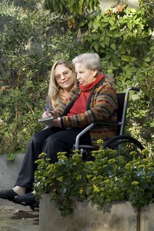 A younger woman is with her elderly mother in a garden.  The older woman is sitting in a wheelchair.  She is smiling and looking away from the camera as her mother writes on a notepad.  Vertically framed shot. Stock Photo