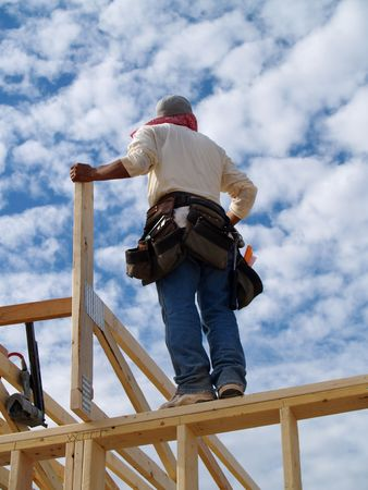 A man is  standing on the wall frame of a house.   His back is facing the camera.   Vertically framed shot. Stock Photo - 3395213