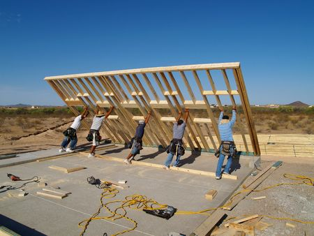 Men are working on building a wall of a house.  They are looking at their work with their backs facing the camera.  Vertically framed shot.