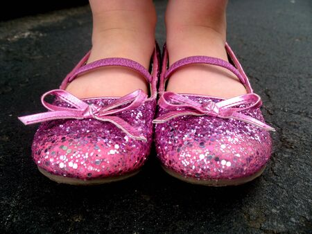 A little girl is wearing pink, sparkly tap shoes.  Horizontally framed shot.