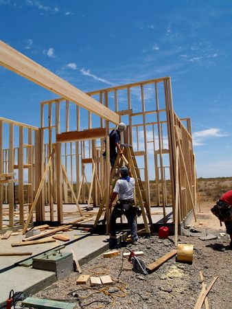 site: Two men are working on building a wall of a house.  They are looking at their work with their backs facing the camera and one man is on a ladder.  Vertically framed shot.