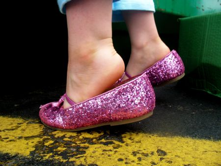 tiptoes: A little girl is wearing pink, sparkly tap shoes.  She is standing on her tiptoes.  Horizontally framed shot.