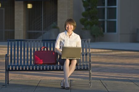 A woman smiling with her notebook PC on her lap, as she sits on a public bench. Horizontally framed shot. photo