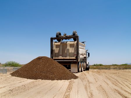 A dump truck is dumping a mound of dirt onto an excavation site.  Horizontally framed shot. photo