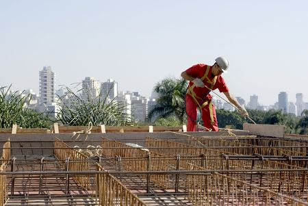 A worker is standing at the top of a building being constructed.  He is hauling materials up to him on a rope.  The site he is working is level with the cities skyline.  Horizontally framed shot. photo