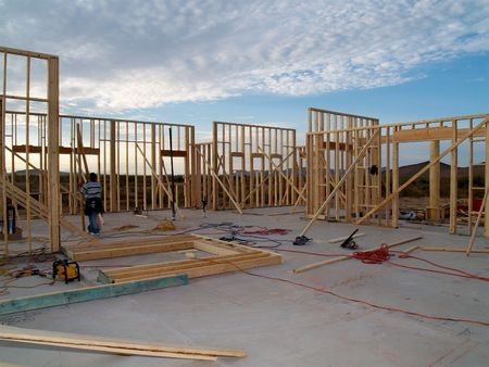 A man is working on building a wall of a house.  He is looking at his work with his back facing the camera.  Horizontally framed shot. Stock Photo - 3395255