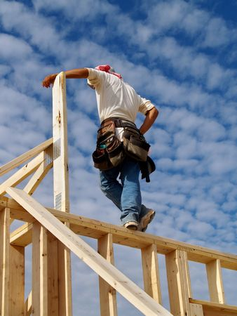A man is  standing on the wall frame of a house.   His back is facing the camera.   Vertically framed shot. Stockfoto