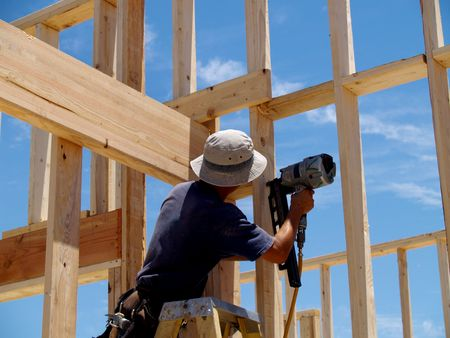 A man is  working on building a wall of a house.   He is on a ladder and his back is facing the camera.   Horizontally framed shot. photo