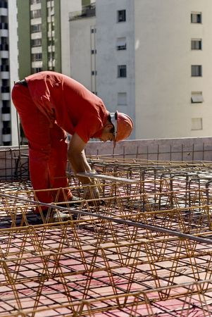 The worker is bent over the metal skeleton of the structure he is working on.  Buildings loom in the background over him.  Vertically framed shot. photo