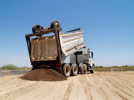 worksite: A dump truck is dumping a mound of dirt onto an excavation site.  Horizontally framed shot.