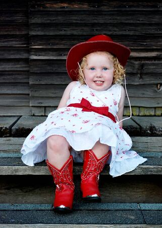 Little girl sitting with a white dress, red cowboy boots and hat. Vertically framed shot. Stock Photo - 3523554