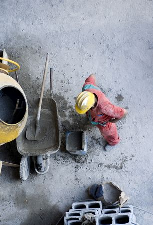 The worker is mixing concrete by cinder blocks in a wheel barrel.  Photo is taking from a vantage point above.  Vertically framed shot.
