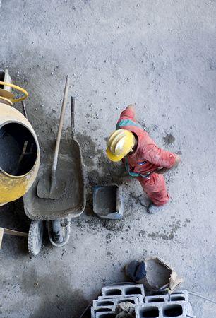 De werknemer is het mengen van beton door as blokken op een wiel vat. Foto nemen van een uitkijkplaats hierboven. Verticaal framed shot.