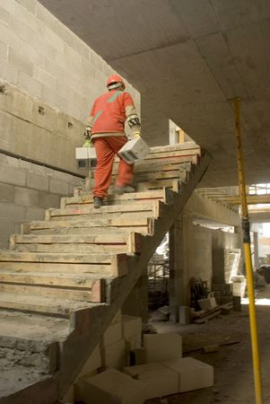 carrying: A construction worker is carrying heavy cinder blocks up the stairs at a construction site.  He has his back facing the camera.  Vertically framed shot.