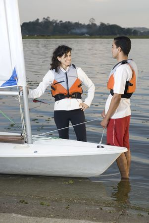 vertically: A young man and woman are standing in the water next to their sailboat.  She is holding onto the sail.  They are smiling and looking at each other.  Vertically framed shot.