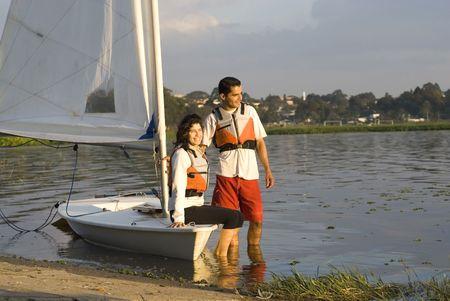 男と女は、ヨットの横にある水に立っています。 話して、お互いを見ています。 水平方向にフレーム ショット。