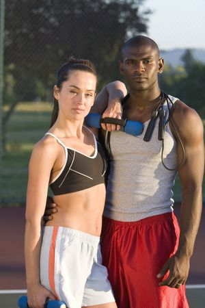 An attractive, fit couple is standing together on a tennis court.  They are holding their workout gear and looking sternly at the camera.  Vertically framed shot.