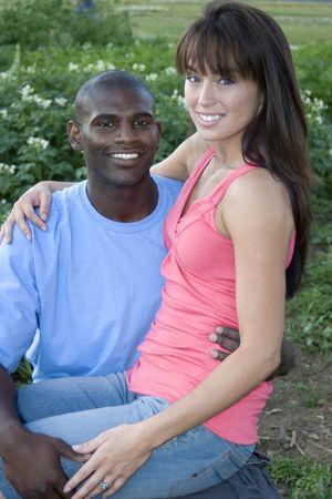 男性と女性が庭で一緒に座っています。 女性は男性の膝の上に座っています。 彼らは微笑し、カメラを見てします。 垂直方向にフレームのショット。