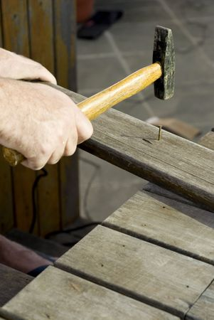 A man, hammering a nail into a piece of wood. Vertically framed shot. photo