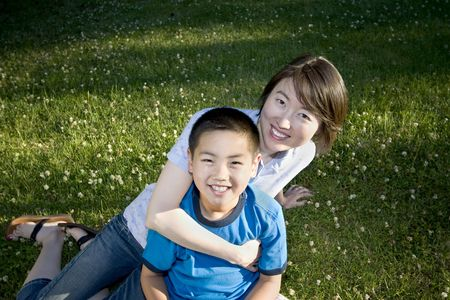 A young child is sitting on his mom's lap in a park.  They are smiling and looking at the camera.  Horizontally framed shot.
