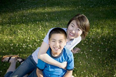 children playground: Un ni�o est� sentado en el regazo de su madre en un parque. Est�n sonriendo y mirando a la c�mara. Horizontalmente enmarcada disparo.