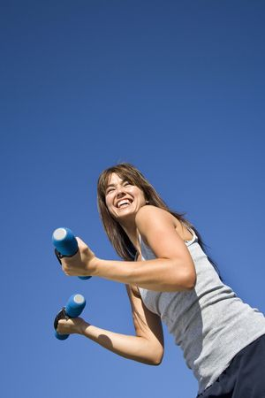 vertically: An attractive, fit woman is working out with hand weights.  She is smiling and looking away from the camera.  Vertically framed shot. Stock Photo