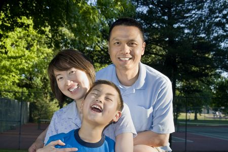 A young family is seated together in a park.  They are smiling and laughing at the camera.  Vertically framed shot. Stock Photo