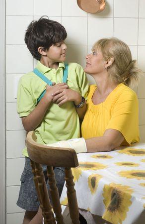 若い男の子は彼の母を抱いています。 彼らはお互いを見て、笑みを浮かべてします。 垂直方向にフレーム ショット。