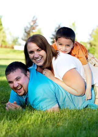 vertically: A happy family is lying in a dog pile on the grass.  They are smiling and looking at the camera.  Vertically framed shot.