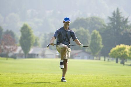 남자 골프 코스에 서 있습니다. 그는 무릎을 꿇고 골프 클럽을 부수고 카메라를 바라 보았다. 가로 프레임 된 샷입니다.