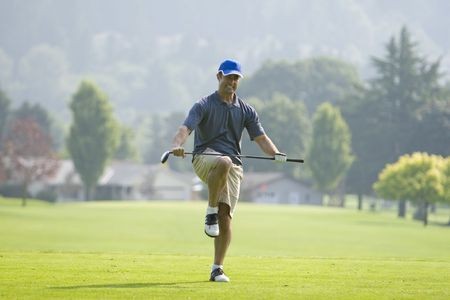 A man is standing on a a golf course.  He is pretending to break the golf club over his knees and looking away from the camera.  Horizontally framed shot.