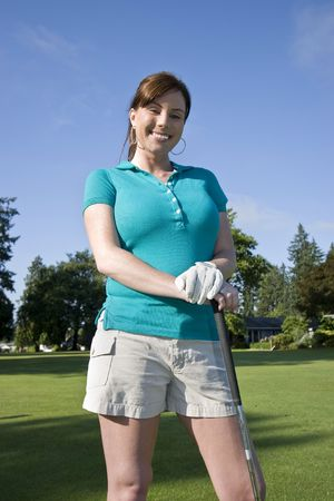 A young woman is standing on a golf course.  She is holding a golf club and smiling at the camera.  Vertically framed shot. Stock Photo