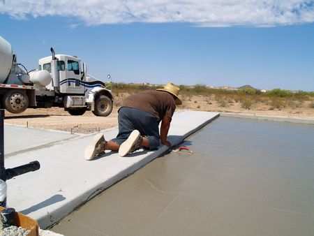 Shot of a construction worker smoothing out a freshly poured concrete slab using a hand trowel. Horizontally framed shot. Stockfoto