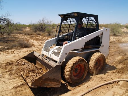 worksite: Construction worker driving a skid steer loader at a desert construction site. Horizontally framed shot. Stock Photo