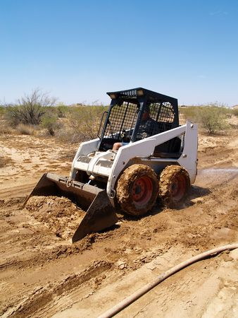 Construction worker driving a skid steer loader at a desert construction site. Vertically framed shot.