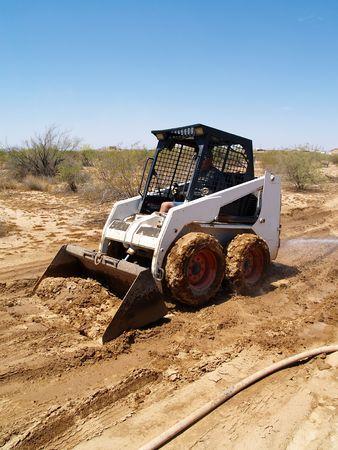 skid steer: Construction worker driving a skid steer loader at a desert construction site. Vertically framed shot.