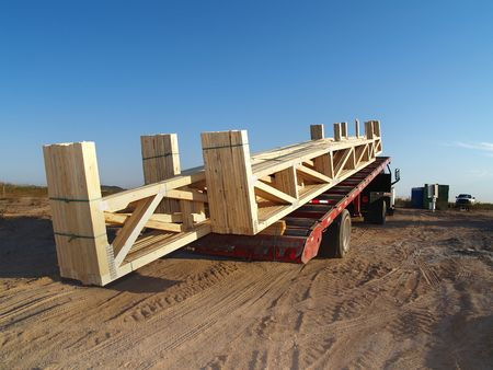 Large truck unloading wooden frame sections at a home construction site. Horizontally framed shot. Stock Photo - 3418452
