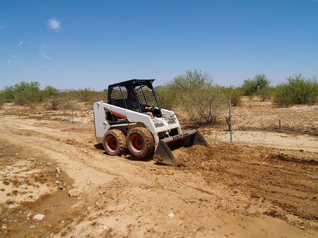 Construction worker driving a skid steer loader at a desert construction site. Horizontally framed shot. Stockfoto